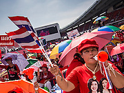 20 NOVEMBER 2013 - BANGKOK, THAILAND: A Red Shirt supporter blows a noise maker and rallies in support of the government. Thousands of Red Shirts, supporters of the Pheu Thai ruling party in Thailand, gathered in Rajamangala Stadium in suburban Bangkok to listen to the Thai Constitutional Court deliver its verdict against the government. The court ruled that the recent efforts by the government to pass a blanket amnesty bill violated the Thai Constitution but the court did not order the party to disband or the dissolution of the government, which had been widely feared.     PHOTO BY JACK KURTZ