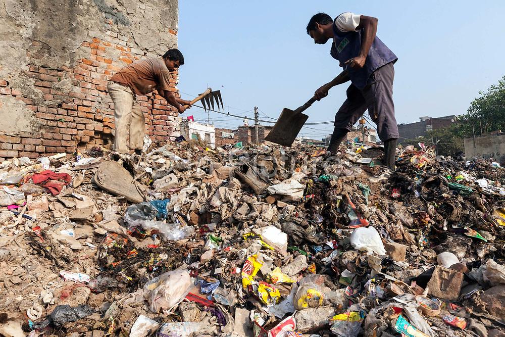 Informal sanitation workers, Ganesh and Pratik  sort and shovel waste on a land fill in the Govindpuri slum, New Delhi, India