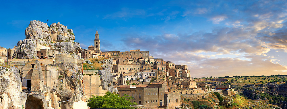 Panoramic view of the ancient Sassi of Matera area exterior, Basilicata, Italy. <br /> <br /> The area of Matera has been occupied since the Palaeolithic (10th millennium BC) making it one of the oldest continually inhabited settlements in the world. <br /> <br /> The town of Matera was founded by the Roman Lucius Caecilius Metellus in 251 BC and remained a Roman town until  was conquered by the Lombards In AD 664 becoming part of the Duchy of Benevento.  Matera was subject to the power struggles of southern Italy coming under the rule of the Byzantine Roman, the Germans and finally Matera was ruled by the Normans from 1043 until the Aragonese took possession in the 15th century. <br /> <br /> At the ancient heart of Matera are cave dwellings known as Sassi. As the fortunes of Matera failed the sassy became slum dwelling and the appalling living conditions became be the disgrace of Italy. From the 1970's families were forcibly removed from the Sassi and rehoused in the new town of Matera. Today tourism has regenerated Matera and the sassi have been modernised and are lived in again making them probably the longest inhabited houses in the world dating back 9000 years. .<br /> <br /> Visit our ROMAN ART & HISTORIC SITES PHOTO COLLECTIONS for more photos to download or buy as wall art prints https://funkystock.photoshelter.com/gallery-collection/The-Romans-Art-Artefacts-Antiquities-Historic-Sites-Pictures-Images/C0000r2uLJJo9_s0<br /> .<br /> <br /> Visit our MEDIEVAL PHOTO COLLECTIONS for more   photos  to download or buy as prints https://funkystock.photoshelter.com/gallery-collection/Medieval-Middle-Ages-Historic-Places-Arcaeological-Sites-Pictures-Images-of/C0000B5ZA54_WD0s