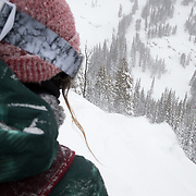 Hadley Hammer watches as Andrew Whiteford turns on a cliff bench full of winter storm powder.
