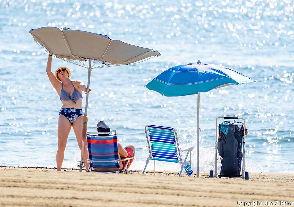A woman adjusts her beach umbrella after a gust of wind turned in inside out.