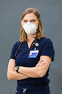 Female doctor in medical scrubs wearing PPE photographed in the studio