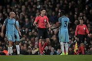 Slavko Vinčić (Referee) speaks to Bacary Sagna (Manchester City) giving him a final warning during the Champions League match between Manchester City and Celtic at the Etihad Stadium, Manchester, England on 6 December 2016. Photo by Mark P Doherty.