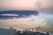 The sun rises at twilight over steaming hot mineral pools at Mammoth Hot Springs, Yellowstone National Park, Wyoming.