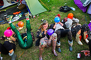 Glastonbury Festival, 2015.<br /> Group of girls all dressed up inhaling baloons of nitrous oxide, or laughing gas, (which gives an instant high) in the camping grounds before the big night out.<br /> Technically laughing gas falls into a legal grey area, coming under the 'legal high' bracket as it is used by some dentists as an anaesthetic. Although it is not illegal to possess and inhale the substance, it is illegal to supply it to anyone under the age of 18.<br /> In an attempt to tackle legal highs, the government's Psychoactive Substances Bill intends to prohibit the sale of mood-altering drugs without a medical purpose.