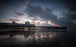 © Licensed to London News Pictures. 04/10/2016. Southsea, Hampshire, UK.  Cloud movement captured in a 30 second exposure as dawn colours light up the sky over South Parade Pier in Southsea this morning, 4th October 2016. Today will be another dry and sunny, but breezy, autumn day in the south of England. Photo credit: Rob Arnold/LNP