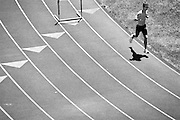 GLASGOW, KY – JULY, 2006: A man runs on a track in bright sunlight.