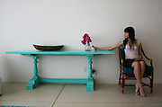 Woman holding purple bugambilia flower, sitting next to turquoise table.<br /> Photo shooting took place in a modern, minimalistically decorated beachfront home in exotic small town of Los Barriles, Baja California Sur, Mexico. <br /> Home decoration is comprised of different color selections, each used with careful combination of details and accompanying furniture, plants and other decorative elements. Prevailing colors are white, red and striking turquoise blue.<br /> Here we are showing photographs from 2 parts of this home; guest bedroom and inner patio, where magnificent red wall with agavas welcomes you upon arrival. And if you are lucky enough to get an invite to stay in the house over night, you will enjoy a beautiful bedroom, with minimal decoration, but very attractive, relaxed and Mexican, but in a contemporary way.