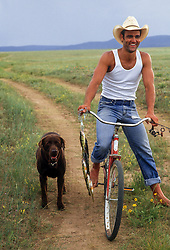 cowboy on a bicycle with a dog and freshly caught fish