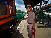 31 MAY 2017 - CHACHOENGSAO, THAILAND: A station master clears a Bangkok bound train to leave the train station in Chachoengsao, a provincial town about 50 miles and about an hour by train from Bangkok. The train from Chachoengsao to Bangkok takes a little over an hour but traffic on the roads is so bad that the same drive can take two to three hours. Thousands of Thais live outside of Bangkok and commute into the city for work on trains, busses and boats.       PHOTO BY JACK KURTZ
