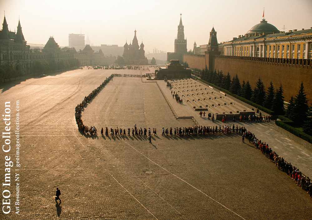 Visitors line up to enter the Lenin Mausoleum in Red Square, Kremlin, Moscow. Some come the night before and sleep in the park; some arrive in the pre-dawn. By 6AM, the Alexander Garden by the north wall is packed with people. Vendors sell ice cream and circular bread (boublik), sleepy children line the park benches while family members hold a place in line. Police shout orders about checking bags, proper dress, staying in twos, keeping silent. About 8:30, a policeman at the front slowly moves the line up the hill into Red Square. Moments before 9, the guard changes and the line is allowed to enter the Mausoleum. Inside it is dark. The line moves down guard lined steps into a cool underground chamber. the guards inspect the crowd and indicate what needs changing. Lenin, wax like, lies in a well lit casket and the surrounding chamber is bathed in dark red light. Guards dressed in brown move the line along. Another guard dressed in forest green is changing in the space near the coffin. The line continues through the morning and finally finishes around 1:PM. The Lenin Mausoleum was built of wood in 1924, and rebuilt of red and black granite in 1930.