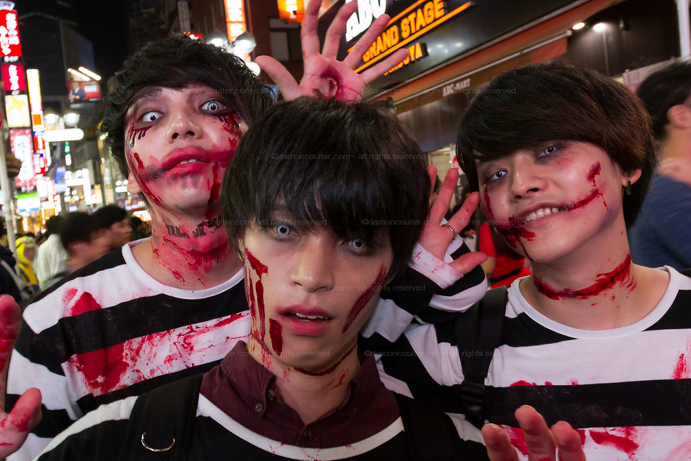 Three young men dressed as prisoners during the Halloween celebrations Shibuya, Tokyo, Japan. Saturday October 27th 2018. The celebrations marking this event have grown in popularity in Japan recently. Enjoyed mostly by young adults who like to dress up, drink , dance and misbehave in parts of Tokyo like Shibuya and Roppongi. There has been a push back from Japanese society and the police to try to limit the bad behaviour.