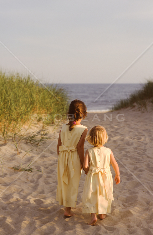 two little girls walking off to the ocean in pretty dresses
