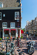 Locals walking and cycling in Keizersgracht in the Nine Streets - De Negen Straatjes - 9 Streetss district of Jordaan, Amsterdam