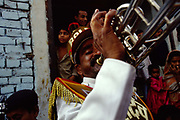 A band member blows his trumpet during a street party in Shadipur. Shadipur Depot, New Delhi, India<br /> The Kathiputli Colony in the Shadipur Depot slum is home to hundreds of (originally Rajasthani) performers. The artistes who live here - from magicians, acrobats, musicians, dancers and puppeteers are often international renowed by always return to the Shadipur slum.