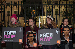 © Licensed to London News Pictures. 22/01/2015. Saudi Arabian Embassy, London, UK. People gather outside the Saudi Arabian Embassy in London on 22 January 2015 to attend the vigil for Raif Badawi, a Saudi Arabian blogger and editor, who has been sentenced to 10 years in prison as well as a punishment of 1,000 lashes, to be delivered in 20 flogging sessions.  The second planned flogging is to be suspended after a medical committee assessed that he should not undergo a second round of lashes on health grounds. Photo credit : Stephen Chung/LNP