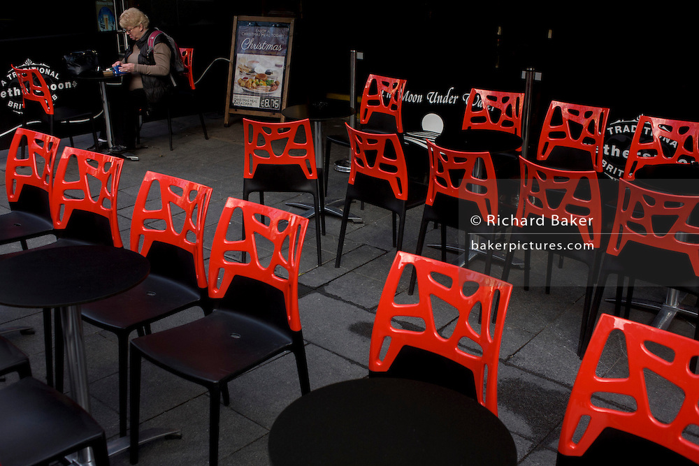 A lone lady diner sits outside on a cold day surrounded by red chair seating.