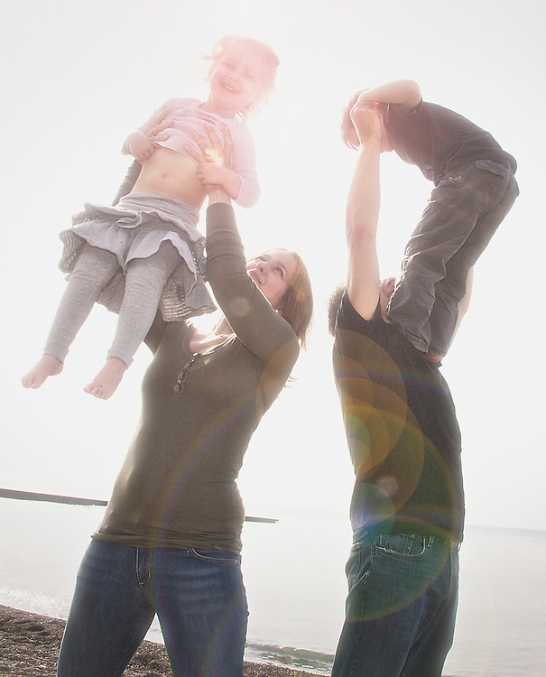Mom and dad play with their children, lifting their daughter and son in the air at the beach.