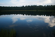 A lake in the sprawling forests of Smaland Småland reflects the sky above in Southern Sweden 4th of August 2016. Smaland is predominatly flat and covered with pine trees and lakes dotted in between.