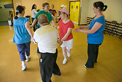Group of Day Service users with learning disability enjoying a line dancing class encouraged by Day Service Assistant clapping,