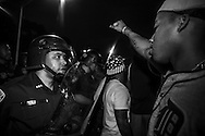 Police in riot grear clash with people protesting against the killing of Alton Sterling.