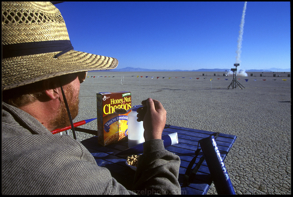 Amateur rocket launch. An amateur rocketeer eats his cereal while watching the launch of a rocket during the annual Black Rock X amateur rocketry event in the Black Rock desert, Nevada, USA. This huge flat expanse of land is a popular launch site for large and powerful amateur rockets as it is far from civilization and has little natural animal or plant life.