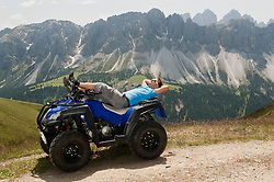 Man sunbathing on Quad bike in mountain landscape