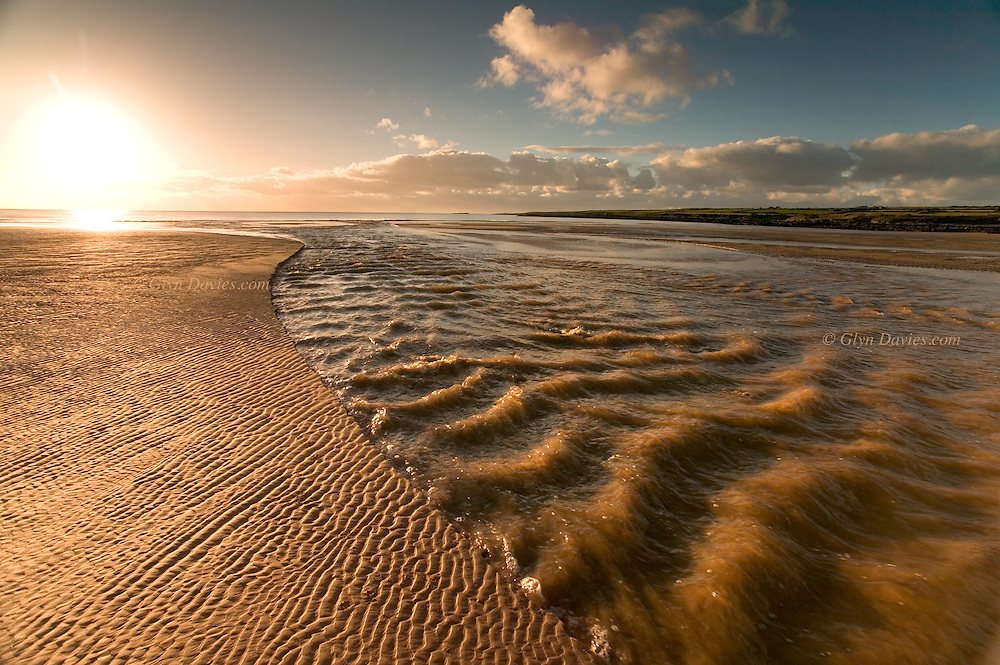 A large and constant river flows from open farmland on Anglesey, past Aberffraw village and out to the sea at the expansive and sandy Aberffraw beach. The wind blowing up the beach creates small standing waves in the river as it rushes against the wind.