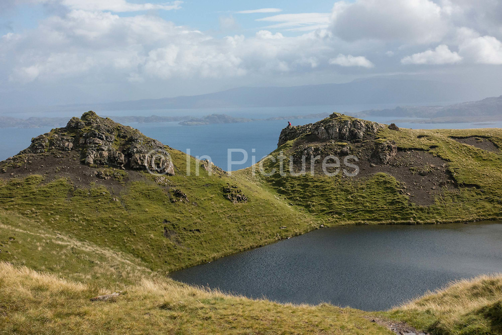 A man sitting on a rock at The Old Man of Storr on the 3rd September 2016 on the Isle Of Skye in Scotland in the United Kingdom. The 'Old Man' is a large pinnacle of rock that stands high and can be seen for miles around. Forming part of the Trotternish ridge, the Storr was created by a massive ancient landslide, and has become a popular walking and tourist destination.
