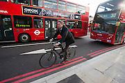 Een man fietst tussen de bussen in Upper Street in de Londense wijk Islington.<br /> <br /> A man is cycling between busses at the Upper Street in London area Islington.