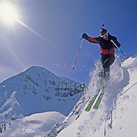 An extreme skier jumps into a seldom-skied chute at Montana's Big Sky Ski Area, with Lone Mountain in the background.