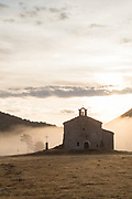 Old stone chapel of Notre Dame de Gratemoine shrouded in fog, Seranon, Provence, France