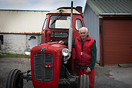 Islander Walter Williams and his Massey Ferguson tractor outside his home at Kiloran Bay on the the Inner Hebridean island of Colonsay on Scotland's west coast.  The island is in the council area of Argyll and Bute and has an area of 4,074 hectares (15.7 sq mi). Aligned on a south-west to north-east axis, it measures 8 miles (13 km) in length and reaches 3 miles (4.8 km) at its widest point, in 2019 it had a permanent population of 136 adults and children.