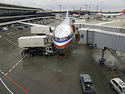 an docked American Airlines airplane being loaded at Narita airport Tokyo Japan