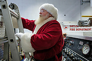 19 DECEMBER 2020 - SAYLOR TOWNSHIP, IOWA: SANTA CLAUS climbs up to his seat on top of a Saylor Township firetruck. The Saylor Township Fire Department welcomed Santa Claus to the township on the north edge of Des Moines by showing him around town a fire engine. The event was organized by the Fire Deparment for the town's youngsters who won't be able to see Santa this year because of the Coronavirus pandemic.     PHOTO BY JACK KURTZ