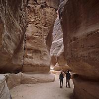 Travelers explore the Siq, a dramatic slot canyon leading to Petra, Jordan.
