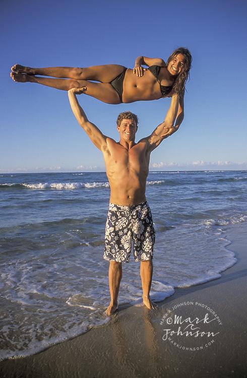 Australia, Queensland, N. Stradbroke Island, man holding woman above his head. people ****Model Release available