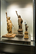 "Two 1870 maquette's by Frédéric Bartholdi for the Statue of Liberty, in terracotta on the left, and bronze in the center, together with an 1879 ""American Committee Model"" in bronze, produced as a money-making souvenir to raise the funds needed to build a pedestal for the statue. The maquettes reflect the evolution of the design for the statue."