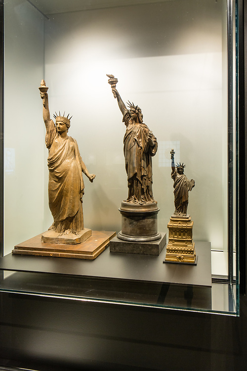 """Two 1870 maquette's by Frédéric Bartholdi for the Statue of Liberty, in terracotta on the left, and bronze in the center, together with an 1879 """"American Committee Model"""" in bronze, produced as a money-making souvenir to raise the funds needed to build a pedestal for the statue. The maquettes reflect the evolution of the design for the statue."""