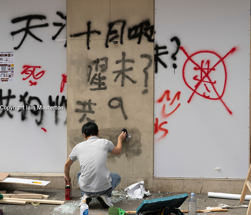 Kowloon, Hong Kong, China,. 7 October, 2019. After a night of violent confrontations between police and pro-democracy protestors in MongKok and YauMaTei in Kowloon, many MTR railway stations and what are thought to be pro-Beijing business franchises were vandalised. Worker removing graffiti at Chinese owned bank.