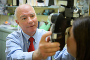 Dr Stephen Allison, a Doctor of Optometry, of Palm City Eye Care, examines the eyes of a young patient in an office setting.