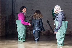 © Licensed to London News Pictures. 07/12/2015. York UK. Picture shows women enter a flooded building in York, the city has flooded for the second time this month after the river Ouse burst it banks last night with the after effects of Storm Desmond. Photo credit: Andrew McCaren/LNP