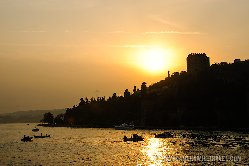 Silhouette against the setting sun of the Rumelian Castle (Rumelihisari), a 15th century fortress on the banks of the Bosphorus in Istanbul, Turkey. In the foreground several small fishing boats try their luck.