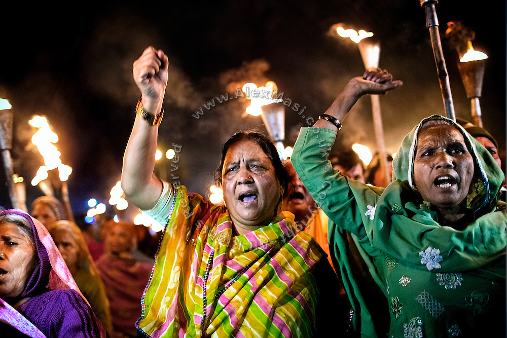 Fist up towards the sky, Rashida Bee, 57, (centre) is demonstrating along other '1984 Gas Survivors' next to the abandoned Union Carbide (now DOW Chemical) industrial complex in Bhopal, central India, on the evening of the 29th anniversary since the infamous 'Gas Disaster', on December 2, 2013. Rashida Bee is the founder of 'Chingari Trust Rehabilitation Centre', one of two vital medical institutions funded by 'The Bhopal Medical Appeal'.