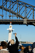 Tourist taking video of the Sydney Harbour Bridge from top deck of a harbour Ferry. Sydney, Australia