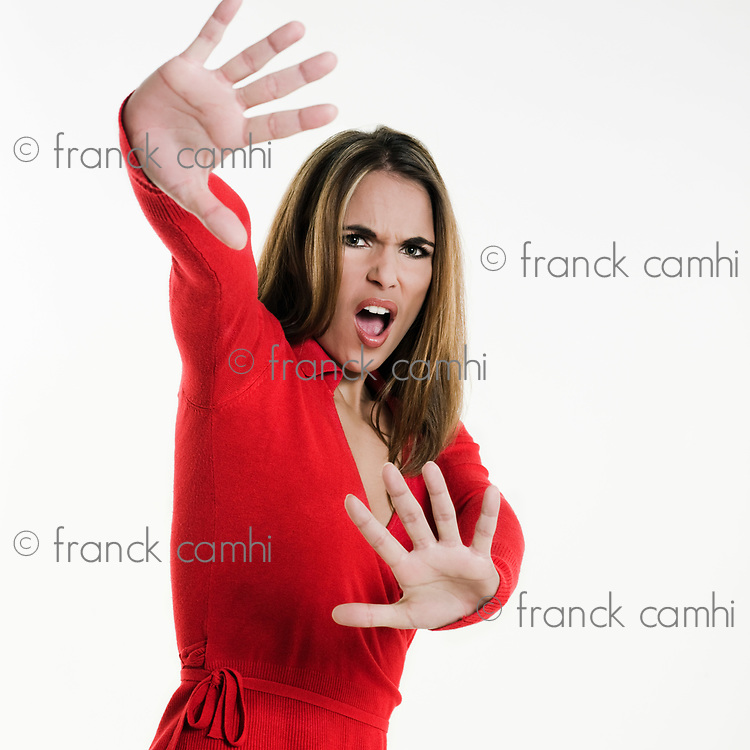 beautiful brunette  woman on white background shielding with her arms