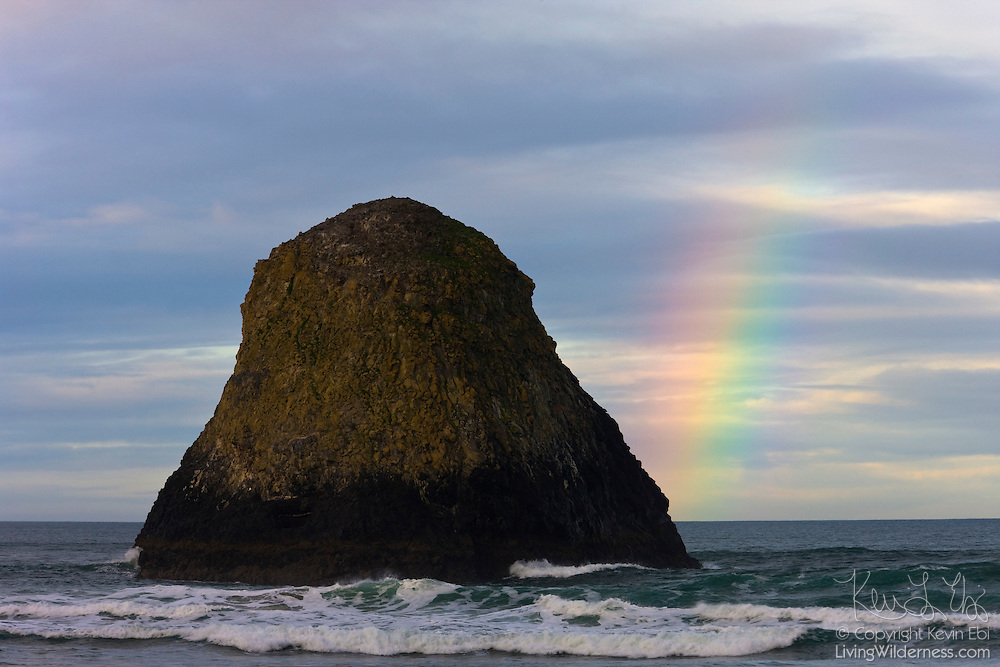 A bright rainbow falls on the base of a prominent sea stack on the Oregon coast. This sea stack is part of the Bird Rocks, a series of sea stacks located off Crescent Beach in Ecola State Park near the town of Cannon Beach.