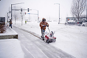 29 DECEMBER 2020 - DES MOINES, IOWA: A worker uses a snowblower to clear the snow off the sidewalk in front of a grocery store in Des Moines during the heaviest snowfall so far of the 2020-21 winter. Des Moines was expected to get about 8 inches of snow before Wednesday morning. Statewide, across Iowa, more than 900 snowplows have been called out to clear the roads.       PHOTO BY JACK KURTZ