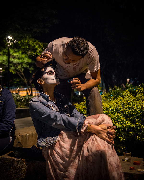 A woman from Colombia gets her face painted at night during Day of the Dead (Dia de los Muertos) festivities in Oaxaca, Mexico.