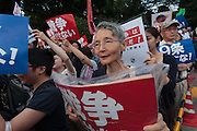 A demo outside the Japanese parliament building against Prime Minister, Shinzo Abe and his reinterpretation of Article 9 of the Japanese Constitution. Nagatacho, Tokyo, Japan. Friday July 17th 2015. Around 10,000 people took part to protest a change in the law that would allow collective self-defence which was ratified in the Lower House on Thursday. Many fear this new interpretation of Japan's unique peace constitution will mean Japanese soldiers being sent to war, to aid allies such as America,